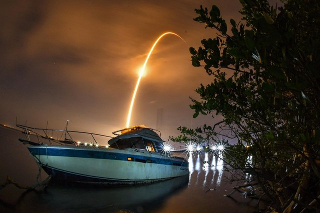 A long exposure shows a streak across the sky above an abandoned boat from the launch of a Falcon 9 rocket and 60 Starlink satellites from Launch Complex 40 at Cape Canaveral Space Force Station, early Wednesday, March 24, 2021, at Port Canaveral in Florida. The 4:28 a.m. launch Wednesday morning lit the skies of the Space Coast with the booster landing on the drone ship Of Course I still Love You. Two and a half minute time exposure of the launch. (Photo by Malcolm Denemark/Florida Today via AP Photo)