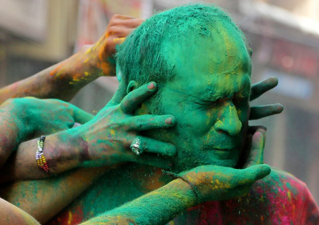 Indians smear colored powder on each other as they celebrate Holi in Jammu, India, Sunday, March 28, 2021. Holi, the Hindu festival of colors, also heralds the arrival of spring. (Photo by Channi Anand/AP Photo)