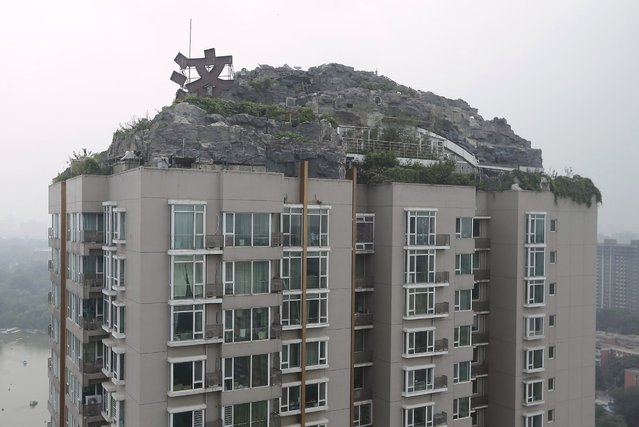 A privately built villa, surrounded by imitation rocks, is pictured on the rooftop of a 26-storey residential block in Beijing, August 13, 2013. A resident in the building has spent more than six years to build a villa covering over 1,000 square meters (10,764 square feet) on top of a 26-storey building in Beijing, according to local media. Residents in the building complained about the villa, fearing its weight may cause structural collapse. The local bureau of city administration attempted to investigate the allegedly illegal construction, but the owner has not shown up so far, Xinhua News Agency reported. (Photo by Jason Lee/Reuters)