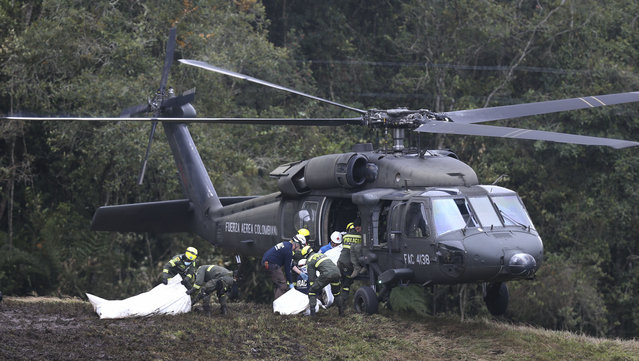 Rescue workers place the bodies of victims of an airplane crash into a waiting helicopter, in La Union, near Medellin, Colombia, Tuesday, November 29, 2016. The chartered plane was carrying a Brazilian soccer team to the biggest match of its history when it crashed into a Colombian hillside and broke into pieces, killing 75 people and leaving six survivors, Colombian officials said Tuesday. (Photo by Fernando Vergara/AP Photo)