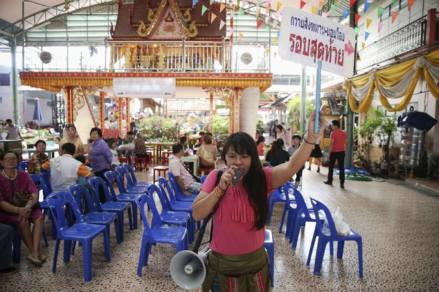 "A woman holds a sign reading ""Offering alms, sleeping in coffins, last round"" as she invites people at Wat Takien temple in Nonthaburi province, on the outskirts of Bangkok February 14, 2015. (Photo by Damir Sagolj/Reuters)"