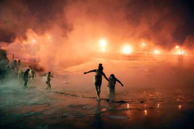 """2013. Members of the Walrus Club enjoy a dip in an icy lake. A popular pastime is to take a dip in holes cut into the ice and then retire to a """"banya"""" (sauna) that is heated with steam from the nearby power plant. (Photo by Elena Chernyshova)"""