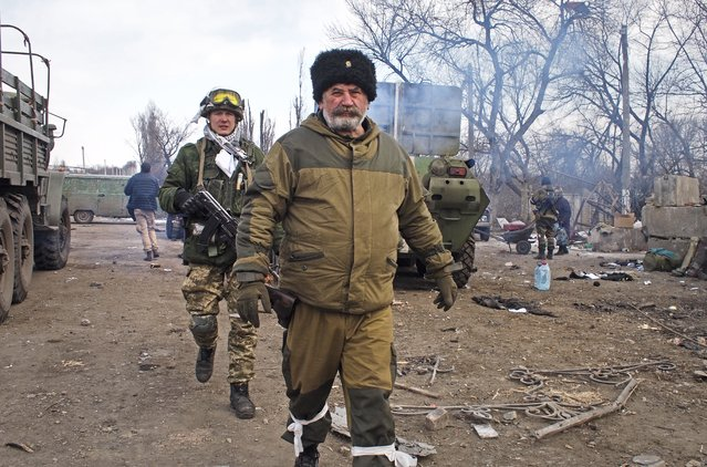 """Cossack commander Nikolai Kozitsyn, foreground, a Russian national known to his fellow rebel fighters by the nom de guerre """"Daddy"""", walks through a crossroads by the east Ukraine town of Debaltseve on Thursday, February 19, 2015. The town was captured by Russian-backed separatists this week after weeks of bitter battles around the area. (Photo by Peter Leonard/AP Photo)"""