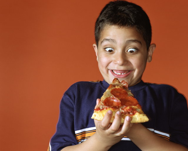 Boy (7-9) smiling while looking down at slice of pepperoni pizza. (Photo by Ryan McVay/Getty Images)