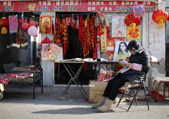 A vendor, selling traditional decorations for the upcoming Chinese Lunar New Year, reads a newspaper as she waits for customers at a migrant workers' village in Beijing February 12, 2015. (Photo by Kim Kyung-Hoon/Reuters)