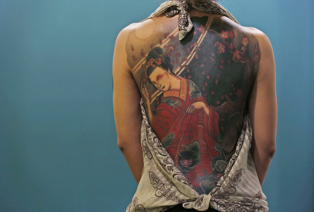 A woman shows her tattooed body during the first International Hong Kong China Tattoo Convention, on October 4, 2013. The tattoo artists from around the world will participate in the convention which runs from October 4 to 6. (Photo by Kin Cheung/Associated Press)