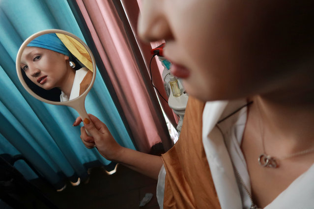 "Makeup artist He Yuhong, also known as ""Yuya"", checks herself in the mirror during a photo shoot following her transformation into the ""Girl with a Pearl Earring"", the 17th century oil painting by Dutch painter Johannes Vermeer, at her house in Chongqing, China on August 14, 2018. (Photo by Thomas Suen/Reuters)"