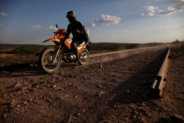 A man rides a motorcycle on the partially constructed Transnordestina railway track in Missao Velha, Ceara state, Brazil, October 25, 2016. (Photo by Ueslei Marcelino/Reuters)