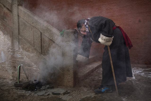 A Tibetan Buddhist woman prays in juniper smoke during Monlam or the Great Prayer rituals on March 3, 2015 at the Labrang Monastery, Xiahe County, Amdo, Tibetan Autonomous Prefecture, Gansu Province, China. (Photo by Kevin Frayer/Getty Images)