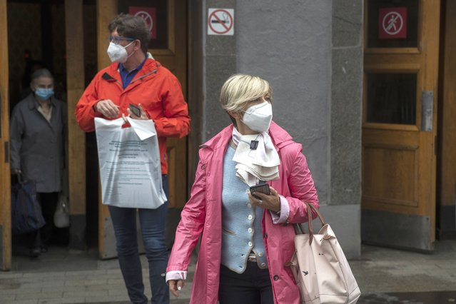People wearing face masks exit a metro station in Moscow, Russia, Thursday, July 10, 2021. The Russian authorities reported a spike in coronavirus infections on Thursday, with new confirmed cases exceeding 11,000 for the first time since March. (Photo by Pavel Golovkin/AP Photo)