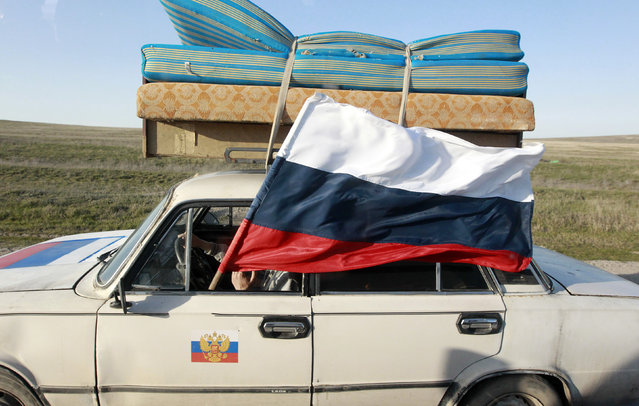 A car drives with a Russian flag on a road outside the port city of Feodosia March 24, 2014. (Photo by Shamil Zhumatov/Reuters)