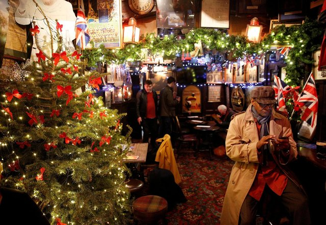 People patronise The Churchill Arms pub, which has been illuminated and covered in Christmas decorations, in London, Britain December 20, 2016. (Photo by Neil Hall/Reuters)