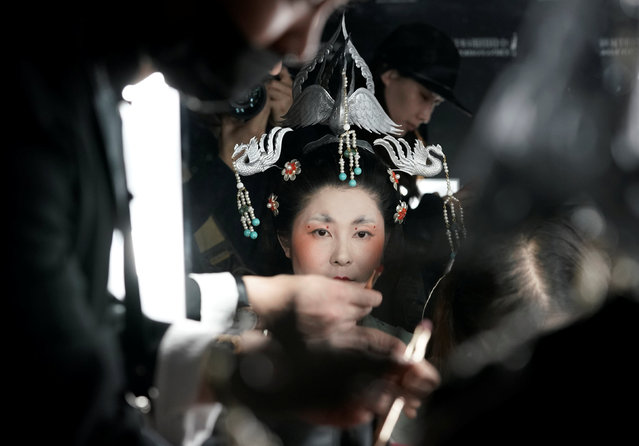 A performer has make-up applied backstage before a show by designer Chu Yan at China Fashion Week in Beijing, China, October 30, 2018. (Photo by Jason Lee/Reuters)