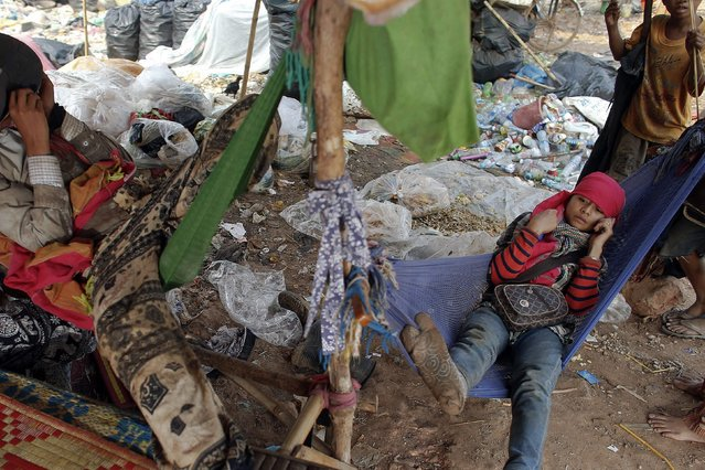 People who work at a landfill dumpsite outside Siem Reap rest in hammocks as they wait for a garbage truck to arrive March 19, 2015. (Photo by Athit Perawongmetha/Reuters)