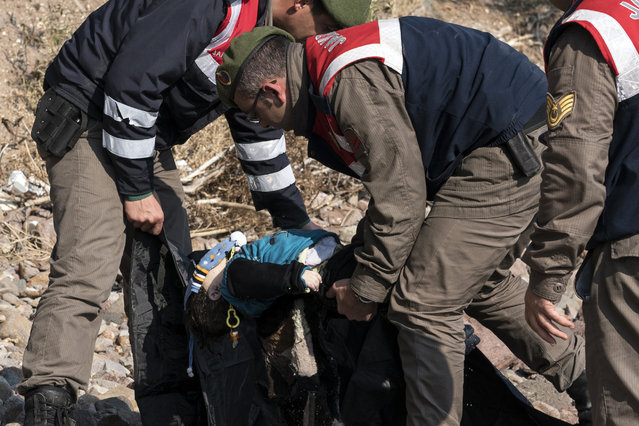 Turkish paramilitary police officers collect the dead body of a migrant boy from the beach near the Aegean town of Ayvacik, Canakkale, Turkey, Saturday, January 30, 2016. (Photo by Halit Onur Sandal/AP Photo)