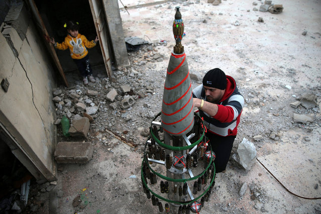 Akram Abu al-Foz decorates a Christmas tree with empty shells which he painted, in the rebel held besieged city of Douma, in the eastern Damascus suburb of Ghouta, Syria December 23, 2016. (Photo by Bassam Khabieh/Reuters)