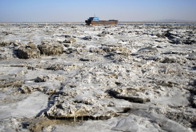 A boat is stranded in the frozen Yellow Sea in Dandong, Liaoning province, China, January 25, 2010. (Photo by Reuters/Stringer)