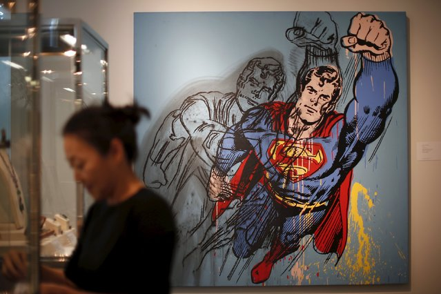 """A woman stands in front of Andy Warhol's """"Superman"""", which is expected to fetch USD $6-8 million at a pre-auction viewing at Sotheby's in Los Angeles, California March 25, 2015. (Photo by Lucy Nicholson/Reuters)"""