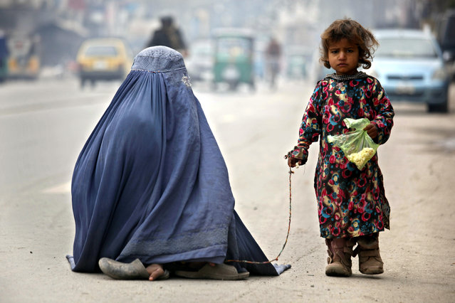 A burqa-clad mother and her daughter begs for alms on a road in Peshawar, Pakistan, 08 May 2016. Mother's day is celebrated on second Sunday of  May in a large number of countries to honour mothers and for appreciation of motherhood. (Photo by Arshad Arbab/EPA)