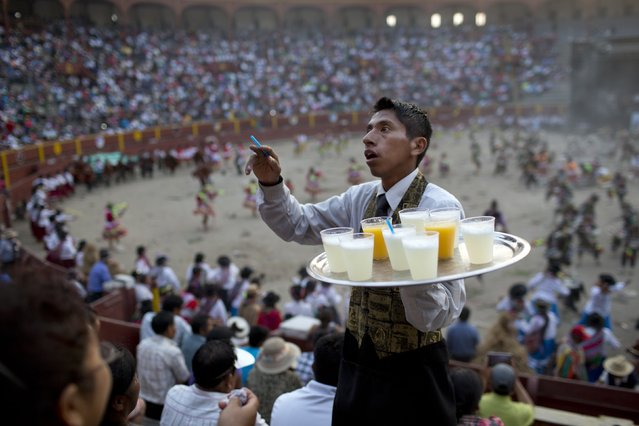 In this Sunday, March 29, 2015 photo, a vendor sells pisco sours and servings of orange juice, in the stands of the Acho bullring, during the Vencedores de Ayacucho dance festival, in Lima, Peru. While most of those attending the festival consume a fermented corn drink called chicha, those who can afford it drink the pricier pisco sour, which is a cocktail made from a colorless or yellowish-to-amber colored brandy, produced in wine making regions of Peru and Chile, mixed with citrus juice and sweeteners. (Photo by Rodrigo Abd/AP Photo)