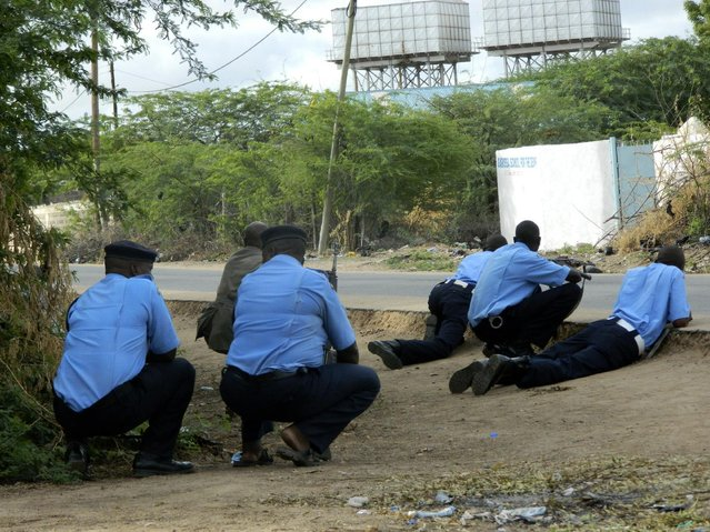 Kenyan police officers take cover outside the Garissa University College during an attack by gunmen in Garissa, Kenya, Thursday, April 2, 2015. Gunmen attacked the university early Thursday, shooting indiscriminately in campus hostels. Police and military surrounded the buildings and were trying to secure the area in eastern Kenya, police officer Musa Yego said. (Photo by AP Photo/Stringer)