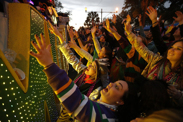 Parade-goers vie for beads and trinkets as the Krewe of Endymion Mardi Gras parade rolls through New Orleans, Saturday, February 6, 2016. (Photo by Gerald Herbert/AP Photo)