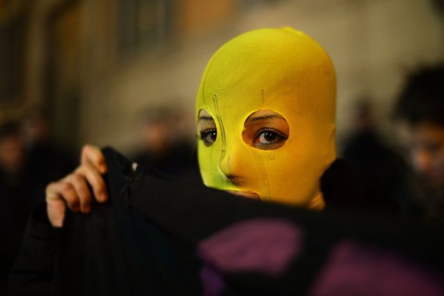 A protestor wears a yellow hood as she demonstrates against the prison sentences of the Russian band p*ssy Riot, as well as shows support for human rights in Russia on November 25, 2013 near the Quirinale, the Italian President's residence, during a visit of Russia's President Vladimir Putin in Rome. (Photo by Filippo Monteforte/AFP Photo)