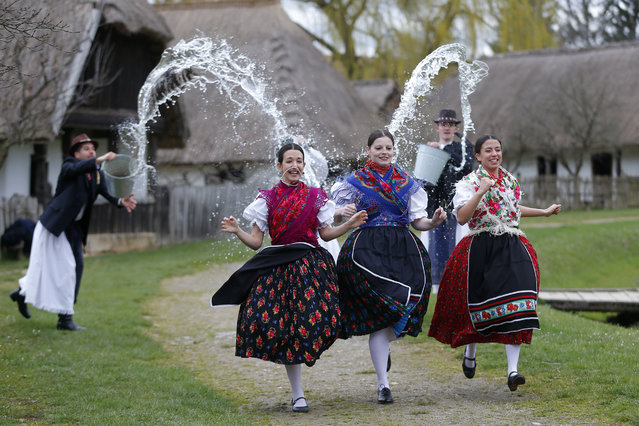 """Women run as men throw water at them as part of traditional Easter celebrations, during a media presentation in Szenna, Hungary, April 3, 2015. Locals celebrate Easter with the traditional """"watering of the girls"""", a fertility ritual rooted in Hungarian tribes' pre-Christian past, going as far back as the second century after Christ. (Photo by Laszlo Balogh/Reuters)"""
