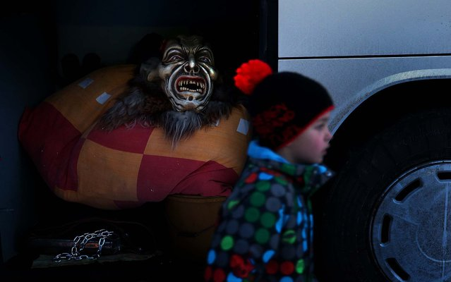 A young boy walks past a hand-crafted Krampus mask and other elements of the Krampus creature lying in the hold of a bus as participants prepare to dress in Neustift im Stubaital, Austria. Sixteen Krampus groups including over 200 Krampuses participated in the first annual Neustift event. (Photo by Sean Gallup)