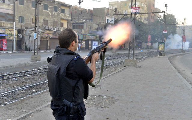A riot policeman fires tear gas during clashes following a demonstration of Muslim Brotherhood and ousted president Mohammed Morsi supporters on December 6, 2013 in the streets of El Zeitun neighborhood close by al Qubba presidential Palace in Cairo. (Photo by Mohamed El-Shahed/AFP Photo)