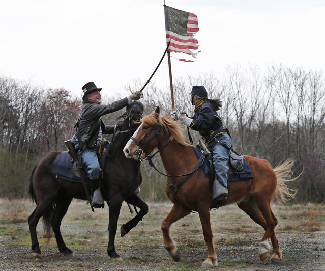 Confederate and Union forces clash during a re-enactment of the Battle of Appomattox Station, Wednesday, April 8, 2015, as part of the 150th anniversary of the surrender of the Army of Northern Virginia to Union forces at Appomattox Court House, in Appomattox, Va. (Photo by Steve Helber/AP Photo)