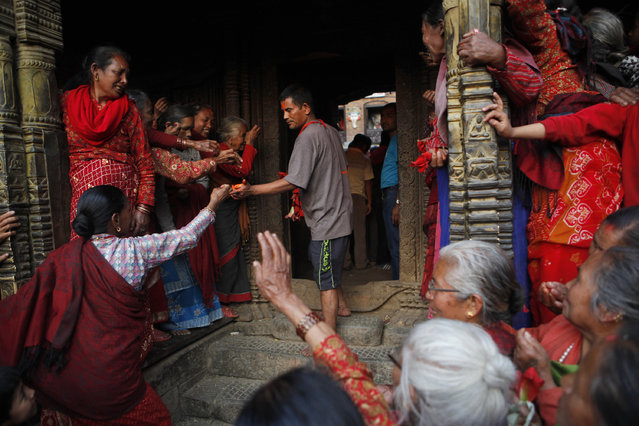 A Hindu priest holds blessed vermillion paste and distributes it to women to apply on their foreheads during Bisket Jatra Festival in Bhaktapur, Nepal, Friday, April 10, 2015. During the festival, also regarded as Nepalese New Year, images of Hindu God Bhairava and his female counterpart Bhadrakali are enshrined in two large chariots and pulled to an open square after which rituals and festivities are performed. (Photo by Niranjan Shrestha/AP Photo)