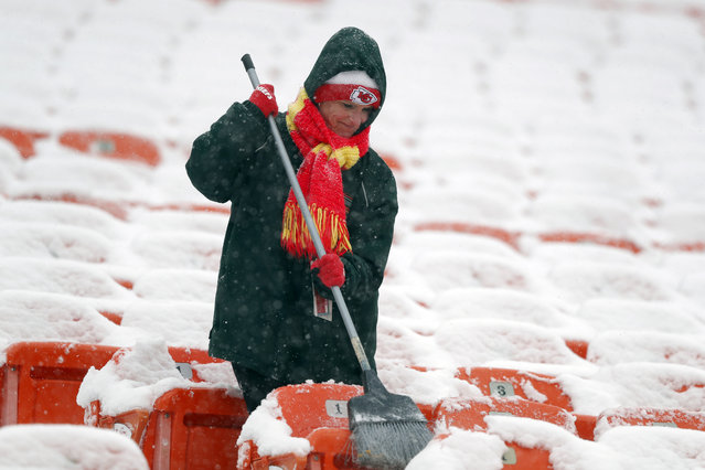 A groundskeeper brushes snow off of seats at Arrowhead Stadium before an NFL divisional football playoff game against the Indianapolis Colts in Kansas City, Mo., Saturday, January 12, 2019. (Photo by Charlie Neibergall/AP Photo)