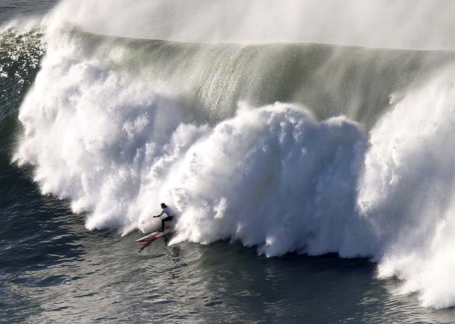 A surfer rides a wave during the Punta Galea Big Wave Challenge in Punta Galea, Spain, on December 22, 2013. The best big wave riders in the world battled against six local wildcards from the Basque Country. American surfer Grant Baker won the competition.  (Photo by Joseba Etxaburu/Reuters)