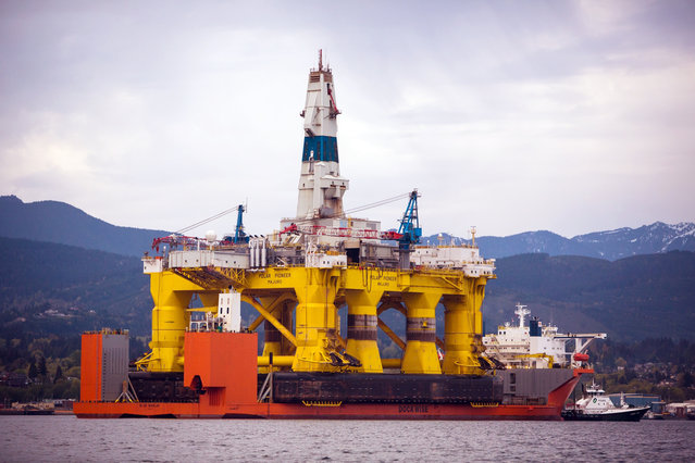 An oil drilling rig arrives aboard a transport ship, following a journey across the Pacific, Friday, April 17, 2015, in view of the Olympic Mountains in Port Angeles, Wash. (Photo by Daniella Beccaria/Seattlepi.com via AP Photo)