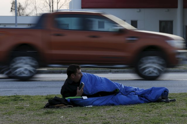 A migrant takes a rest at a petrol station near the town of Polikastro, Greece February 23, 2016. (Photo by Marko Djurica/Reuters)