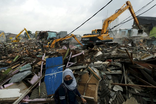 A reporter walks near the ruins of demolished buildings at Kalijodo red-light district in Jakarta, Indonesia, February 29, 2016. Bulldozers started demolishing hundreds of buildings in the Indonesian capital's largest red-light district on Monday as part of a nationwide effort to eradicate prostitution in the world's most populous Muslim-majority nation. (Photo by Reuters/Beawiharta)