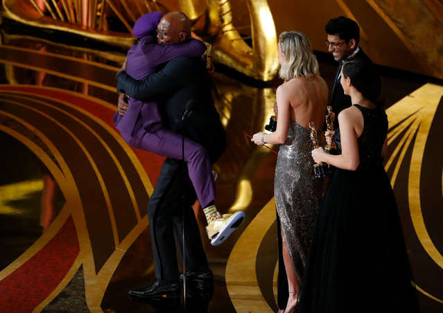 Spike Lee jumps into the arms of presenter Samuel L Jackson as he wins the best adapted screenplay award for BlacKkKlansman during the 91st Annual Academy Awards at Dolby Theatre on February 24, 2019 in Hollywood, California. (Photo by Mike Blake/Reuters)