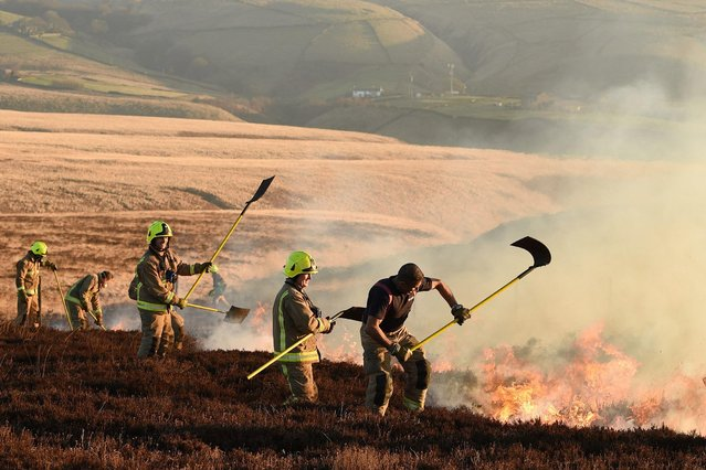 Firefighters tackle a blaze on moorland above Marsden, northwest England on February 27, 2018. (Photo by Oli Scarff/AFP Photo)