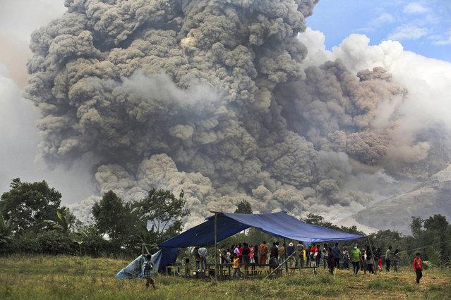 Villagers watch as Mount Sinabung erupts in Perteguhan, North Sumatra, Indonesia, Tuesday, January 14, 2014. (Photo by Binsar Bakkara/AP Photo)