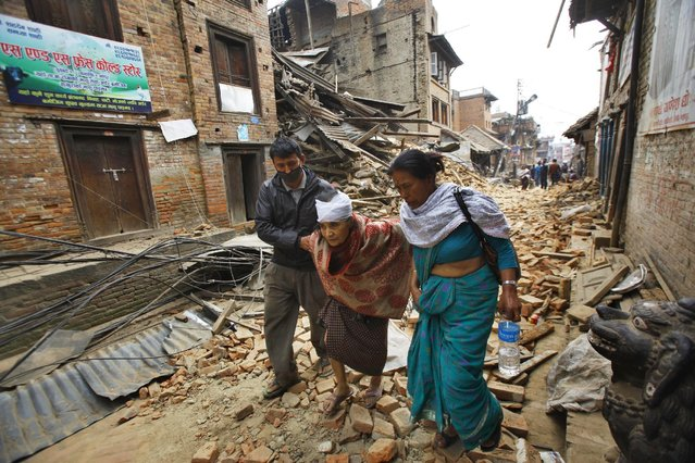 An elderly injured woman is taken to her home after treatment in Bhaktapur near Kathmandu, Nepal, Sunday, April 26, 2015. (Photo by Niranjan Shrestha/AP Photo)