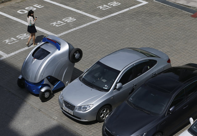 """A woman walks past folded """"Armadillo-T"""", a foldable electric vehicle, at the Korea Advanced Institute of Science and Technology (KAIST) in Daejeon, South Korea Wednesday, September 4, 2013. With a click on a smartphone, the experimental """"Armadillo-T"""" electric car made in South Korea will park itself and fold nearly in half, freeing up space in crowded cities. (Photo by Kim Hong-Ji/Reuters)"""