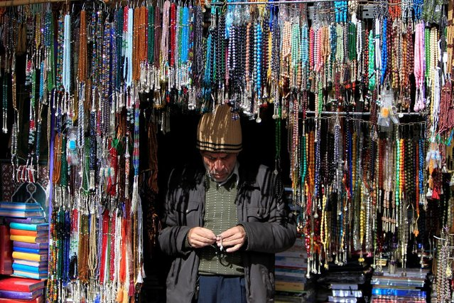 A vendor stands under prayer beads displayed for sale in Damascus, Syria January 27, 2017. (Photo by Ali Hashisho/Reuters)