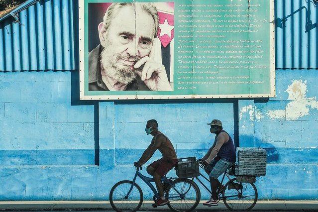 """In this file photo men ride on their bicycles near a poster of Cuban late leader Fidel Castro in Havana, on July 12, 2021. The United States on July 13, 2021 urged Cuba to end internet restrictions imposed after unprecedented protests and renewed a call for the release of detained demonstrators. """"We call on Cuba's leaders to demonstratate restraint (and) respect for the voice of the people by opening all means of communciation, both online and offline"""", State Department spokesman Ned Price told reporters. (Photo by Yamil Lage/AFP Photo)"""