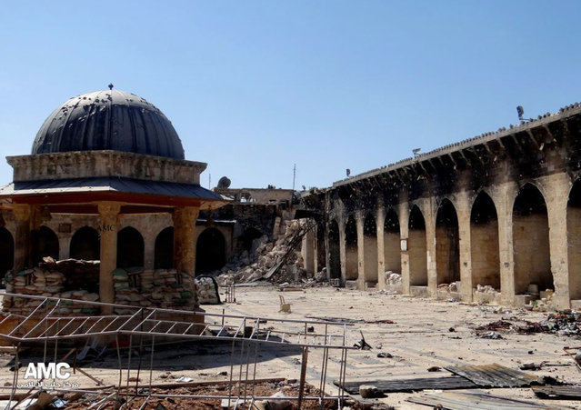 This Wednesday, April 24, 2013 photo, provided by the Aleppo Media Center, which has been authenticated based on its contents and other AP reporting, shows the 12th century Umayyad mosque and the remains of its minaret in the background right corner, after it was destroyed by shelling in Aleppo, Syria. (Photo by AP Photo/Aleppo Media Center)
