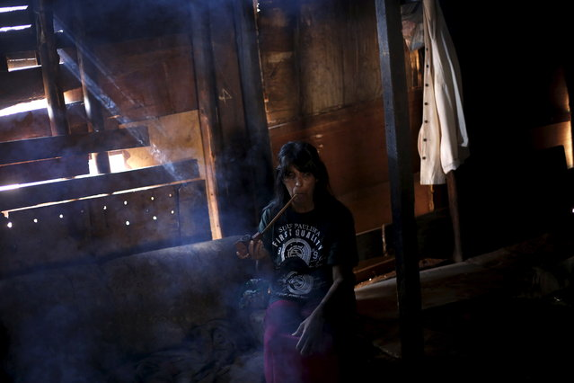 A Guarani Indian woman smokes a pipe in the village of Pyau at Jaragua district, in Sao Paulo April 27, 2015. (Photo by Nacho Doce/Reuters)