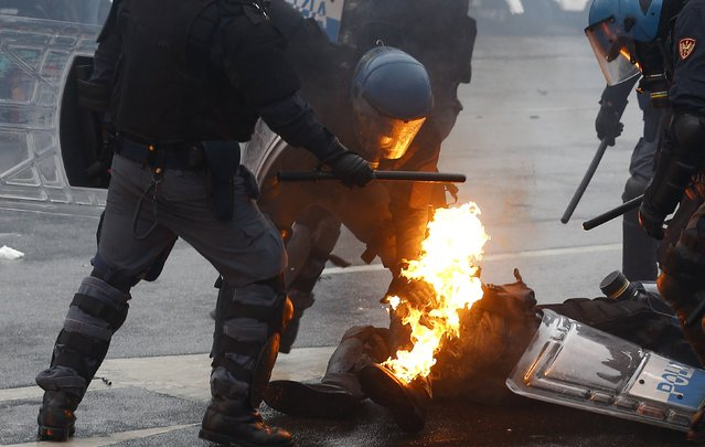 Policemen help their colleague caught on fire after being hit by a molotov bomb during a rally against Expo 2015 in Milan, Italy, May 1, 2015. (Photo by Stefano Rellandini/Reuters)