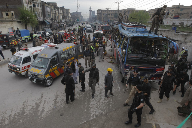 Volunteers and Pakistani security personnel surround a bus following a bomb blast in Peshawar, Pakistan, Wednesday, March 16, 2016. (Photo by Mohammad Sajjad/AP Photo)