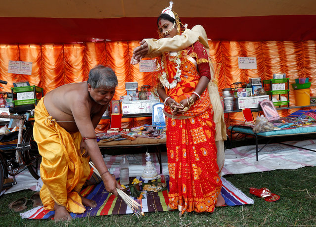 A Hindu priest performs a ritual as a couple take their wedding vows during a mass marriage ceremony in which, according to its organizers, 109 tribal, Muslim and Hindu couples from various villages across the state took their wedding vows, at Bahirkhand village, north of Kolkata, February 5, 2017. (Photo by Rupak De Chowdhuri/Reuters)