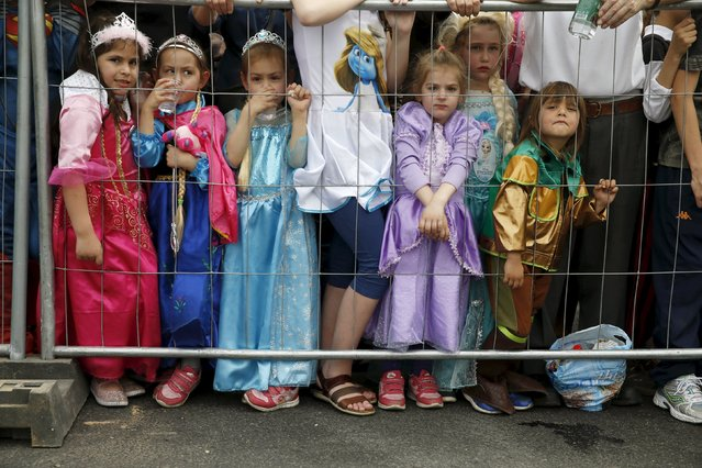 Children wearing costumes watch a parade marking the Jewish holiday of Purim in Petah Tikva near Tel Aviv, Israel March 24, 2016. (Photo by Baz Ratner/Reuters)